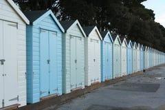 Eine Reihe von weißen und blauen Strandhütten in Mudeford Quay, Großbritannien Lizenzfreie Stockfotografie