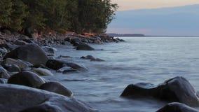 Eine reine Spekulation hinunter Rocky Shoreline During des Oberen Sees ein Sommer-Sonnenuntergang Timelapse stock video footage