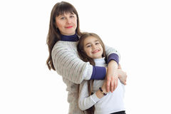 Eine reizend junge Frau, die ihre wenig Tochter und Lächeln umarmt Lizenzfreies Stockfoto