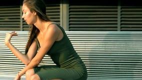 Eine reizend junge Frau mit dem langen Haar, das auf einer Bank in einem Kleid sitzt stock video footage