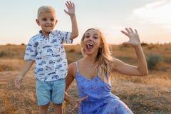 Eine reizend junge Frau mit einem entzückenden Sohn, der ihre Palmen auf einem Himmelhintergrund zeigt Mutter- und Kinderkonzept Stockbild