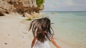 Eine reizend und glückliche philippinische Jugendliche in einem weißen Sommerkleid läuft entlang einen tropischen Strand nahe den lizenzfreies stockfoto