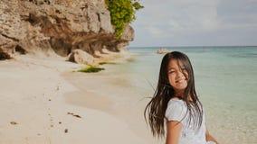 Eine reizend und glückliche philippinische Jugendliche in einem weißen Sommerkleid läuft entlang einen tropischen Strand nahe den stockfoto