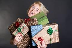 Eine reizende Frau, die Kästen eines viele Geschenks anhält Lizenzfreies Stockbild