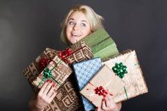 Eine reizende Frau, die Kästen eines viele Geschenks anhält Stockfotos