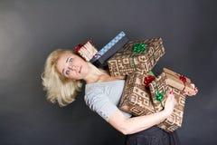 Eine reizende Frau, die Kästen eines viele Geschenks anhält Stockfotografie