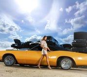 Eine reizende Frau, die nahe bei einem Retro- Auto aufwirft Lizenzfreie Stockbilder