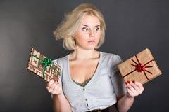 Eine reizende Frau, die zwei Geschenkkästen anhält Stockfotos