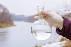 Eine Retorte mit Flusswasserbeispielinnere in der Hand der laboratorians am Landschaftslandschaftshintergrund lizenzfreies stockfoto