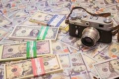 Eine Retro- Kamera auf dem Hintergrund des Geldes Stockbild