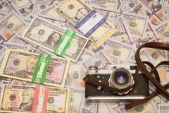 Eine Retro- Kamera auf dem Hintergrund des Geldes Stockbilder