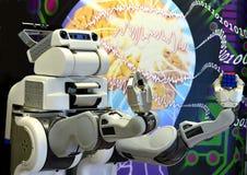Eine Roboterhand, die einen Rubik-` s Würfel mit dem abstrakten Hintergrund hält Lizenzfreie Stockfotos
