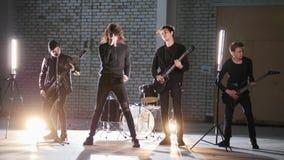 Eine Rockgruppe, die eine Wiederholung in einer Garage hat Mitglieder einer Gruppe, die schwarze Kleidung trägt lizenzfreie stockbilder