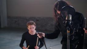 Eine Rockgruppe, die eine Wiederholung hat Ein Mann mit dem langen Haar, das den Gurt zu seiner Gitarre befestigt stock footage