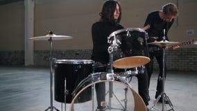 Eine Rockgruppe, die eine Wiederholung hat Ein Mann mit dem langen Haar, das Trommeln spielt stock footage
