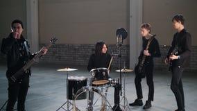 Eine Rockgruppe, die eine Wiederholung hat Ein Mann mit dem langen Haar legt den Rhythmus stock footage
