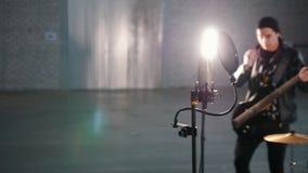 Eine Rockgruppe, die eine Wiederholung hat Ein Mikrofonstand im Fokus stock footage