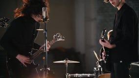 Eine Rockgruppe, die eine Wiederholung hat Ein Solist, der mit seinem langen Haar wellenartig bewegt stock video