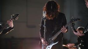 Eine Rockgruppe, die eine Wiederholung hat Ein Solist, der seinen Kopf mit seinem langen Haar rüttelt stock footage