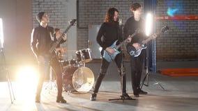 Eine Rockgruppe, die eine Wiederholung hat Gitarristen in der schwarzen Kleidung, die ihre Rollen spielt stock video