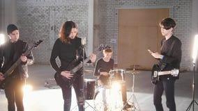 Eine Rockgruppe, die eine Wiederholung hat Leute in der schwarzen Kleidung, die ihre Rollen spielt lizenzfreies stockbild