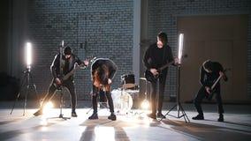 Eine Rockgruppe, die eine Wiederholung hat Leute in der schwarzen Kleidung, die ihre Rollen spielt stock footage