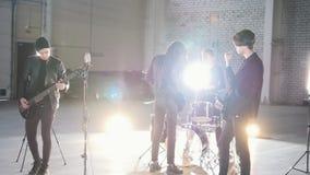 Eine Rockgruppe, die zu einer Wiederholung in einem großen Raum fertig wird stock video footage