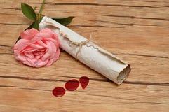 Eine Rolle von Papier binden oben mit Seil und ein rosa stieg Lizenzfreies Stockbild
