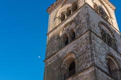 Eine romantische Ansicht eines Turms in Trujillo mit dem Mond, der im einfachen Tageslicht erscheint lizenzfreie stockfotos