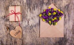 Eine romantische Voraussetzung, ein Umschlag mit Blumen, ein Geschenk und ein hölzernes Herz St Valentinsgruß ` s Tag Lizenzfreie Stockfotos