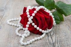 Eine Rose und eine Perlenhalskette Stockfotos