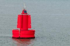 Eine rote Boje, die auf Wasser schwimmt Stockbild