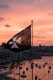 Eine rote Fahne mit den acht zeigte den Stern, der über eine Bucht bei Sonnenuntergang fliegt Stockfotos