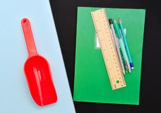 Eine rote Plastikspielzeugschaufel auf dem hellblauen Hintergrund entgegengesetzt Schulausrüstung auf Schwarzem stockfotografie