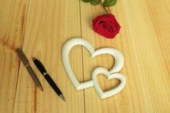 Eine rote Rose mit Stiften Lizenzfreie Stockfotografie