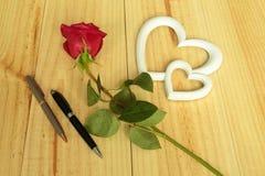 Eine rote Rose mit Stiften Lizenzfreie Stockfotos