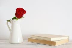 Eine rote Rosenblume in einem weißen Vase Stockbild
