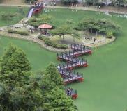 Eine rote Serpentinenbrücke über dem grünen See Stockbild