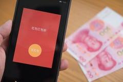 : eine rote Tasche auf Mobile ist bereit, auf WeChat für chinesisches neues Jahr mit RMB auf Hintergrund ausgesendet zu werden Lizenzfreies Stockfoto