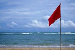 Eine rote warnende Flagge auf dem Strand im Nuca DUA Bali Stockbild