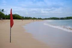 Eine rote warnende Flagge auf dem Strand im Nuca DUA Bali Stockfotos