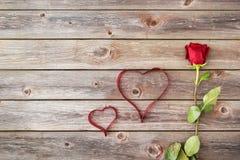 Eine Rotrose auf hölzernem Hintergrund mit Herzen vom Band valenti Stockfotografie