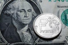 Eine Rubelmünze auf Dollarbanknote Stockbild