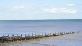Eine ruhige Ebbe an einem sandigen Strand in England während eines heißen Sommers stock footage