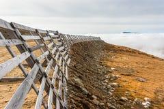 Eine ruhige Gebirgsszene mit Wolkenabdeckung und -zaun auf einem Hügel Lizenzfreie Stockfotografie
