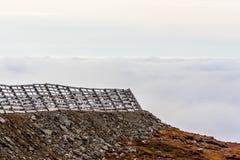 Eine ruhige Gebirgsszene mit Wolkenabdeckung und -zaun auf einem Hügel Stockfoto