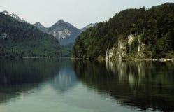 Eine ruhige Szene des Wassers, des Waldes und der bayerischen Alpen Lizenzfreies Stockbild