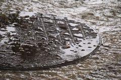 Eine Runde, überschwemmt, Kanaldeckel, Satz während eines harten tropischen Gewitters in Thailand Stockfotografie