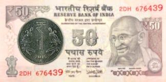Eine Rupienmünze 2015 gegen Banknotengegenstücck der indischen Rupie 50 Stockbild