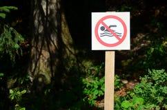 Eine Säule mit einem Zeichen, das ein Verbot auf Schwimmen bezeichnet Das Zeichen zeigt eine gekreuzte-heraus sich hin- und herbe Lizenzfreie Stockfotos